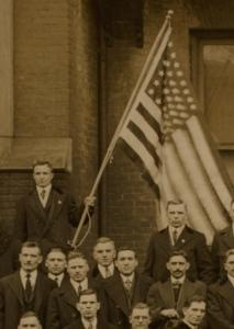Man in a group holding an American flag